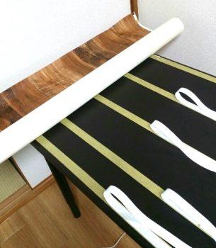 両面テープを少しずつ剥がしながら壁紙を貼る