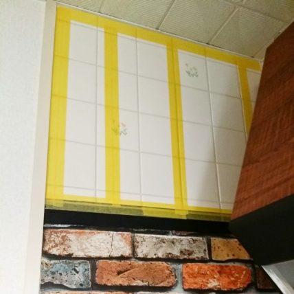 マスキングテープを使ってキッチンの壁に壁紙を貼る