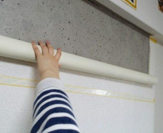 壁紙を巻いて手で押さえる