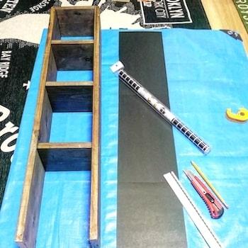 収納棚の大きさに合わせて切り取った厚紙にタイル柄のリメイクシートを貼る準備