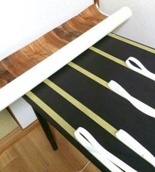 テーブルに貼った超強力両面テープで木目の壁紙を貼っていく