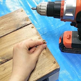 ダボ穴からビスを通して木製の踏み台を固定する
